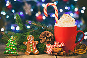 Christmas cappuccino and gingerbread cookies infront Christmas tree on Rustic Wooden Table