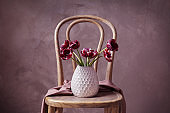 Vase with beautiful tulips on wooden chair
