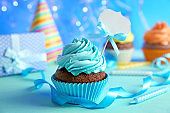 Birthday cupcake with space for text on blurred blue background