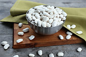 Metal bowl with butter beans on wooden cutting board