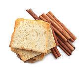 Tasty toasts and cinnamon sticks on white background