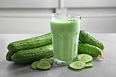 Glass of fresh smoothie and cucumbers on table