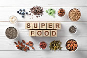 Composition with cubes and assortment of superfood products in bowls on light wooden background