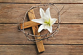 Crown of thorns, wooden cross and white lily on table