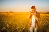 Handsome young traveler man with vintage camera, take a picture of a meadow. Travel mood. Photography. Relaxation on a field and sunset background. Explore nature.