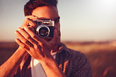 Close-up beautiful portrait of young handsome man with vintage camera, take a picture, on field background, and on sunset. Autumn, summer, mood. Photography