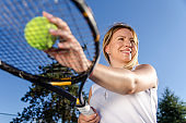 Young woman tennis player preparing for serve