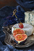 Half of ripe figs with Gorgonzola and Camembert. Close-up. Village.