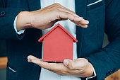 Business man hand hold the house model  saving small house.