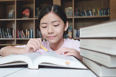 Girl reading and writing in library of school.