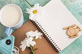 Open notebook, earphones, mug of milk