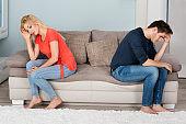 Sad Couple Sitting Back To Back On Sofa