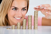 Happy Woman Inserting Coin On The Stacked Of Coins