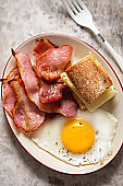 Fried egg, bacon and baguette with mozzarella cheese sandwich. Breakfast plate.