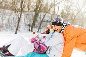Friends sledding in snowy field