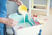 Woman pouring yellow paint into can