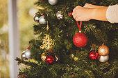 Pregnant woman decorating Christmas tree