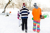Young people carrying snowboards