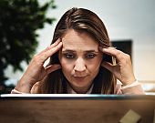 Tired looking blonde office worker stares at computer monitor