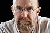 Portrait of serious mature bearded man wearing glasses