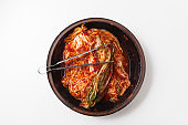 Chopsticks with kimchi in crock head isolated
