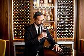 Portrait of handsome elegant businessman drinking red wine in bar