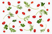Pattern of red mini tomatoes, parsley, dill on white
