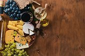 A bottle of wine, and a large assortment of cheeses, honey, nuts and spices, on a wooden table. Top view. Free space for text.