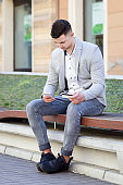 man pay by mobile phone with his credit card while sitting on bench