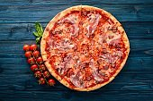 Pizza Lardon. Bacon, cherry tomatoes, sausage salami. On a wooden background. Top view.