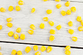 Scattered boiled grain of yellow ripe corn on old rural white wooden planks