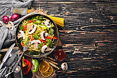Noodles with vegetables in a frying pan. Asian Cuisine Pasta. Top view. Free space. On a wooden background.;
