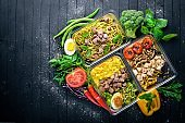 Pasta and buckwheat with meat and fresh vegetables. Healthy Diet Food. Lunch Boxing. On a black wooden background. Top view. Free space for text.