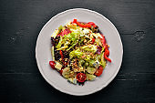 Salad of fresh vegetables and gorgonzola cheese. On a wooden background. Top view. Free space.