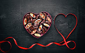 Chocolate box in the form of heart. On a black background Wooden. Top view.