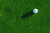 Golf ball on the green course. Close up. Top view. Sport, relax, recreation and leisure concept