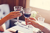 Couple eating romantic Dinner in a gourmet restaurant drinking wine and holding hands