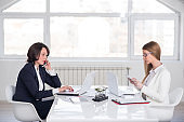 Two woman working in office, using phone and laptop