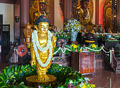 Buddhist statue in temple decorated lights, colorful flowers on Buddha's birthday