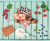 Healthy sandwiches with soft cheese and berries on bread crisps on shabby chic background. Healthy eating and summer gifts concept. Creative food.