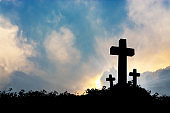 Silhouette of boy praying to a cross with heavenly cloudscape sunset concept for religion, worship, love and spirituality