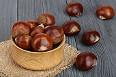chestnut in wooden bowl on black wooden background