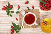 tea with rose hips and honey on white wooden background. Top view