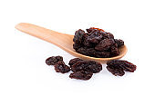 Dried raisin in wooden spoon on white background