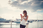 Happy woman on a vacation texting at the marina