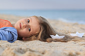 A little girl lies on the seashore. On her wavy hair there are paper boats.