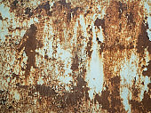Texture of old rusty metal with streaks of rust and cracked, flaking paint. Surface of rusty metal close-up with old and faded paint