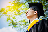 A graduate in the mantle looks up and thinks of a great future. handsomel graduate boy with graduate, Nature background.