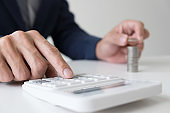 Businessman using calculator to analysis business investment and stacking coins arranged at office desk in modern office, financial concept