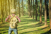 Young Man Traveler with backpack open arm relaxing outdoor on background fir park Summer vacations and Lifestyle hiking concept